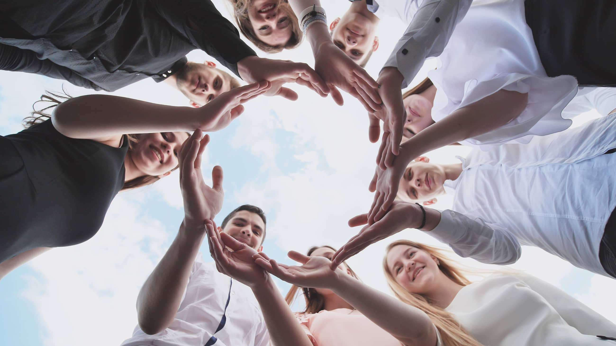 A group of high school students look through the shape of a circle created from their palms. The concept of friendly friends