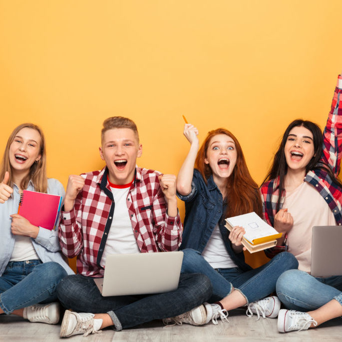 Group of happy school friends doing homework while sitting together on a floor and celebrating over yellow background