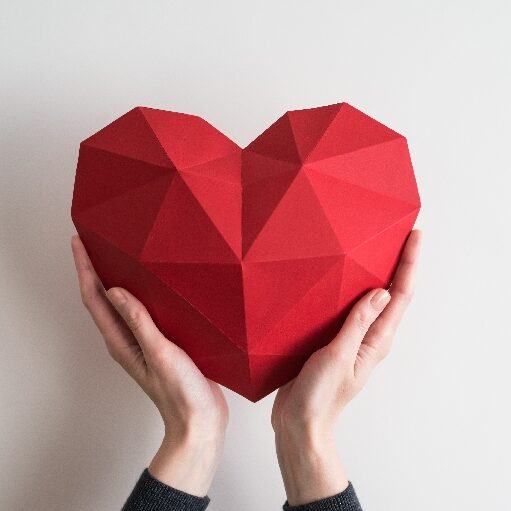 Female hands holding red polygonal paper heart shape